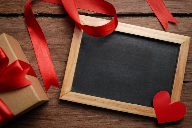 Selektiver fokus der geschenkbox mit rotem band, tafel und liebespapier über rustikalem holztisch, draufsicht flach.