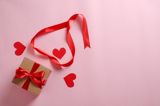 Selektiver fokus der geschenkbox mit rotem band und liebe formte papier über rosa hintergrund; draufsicht flach legen.
