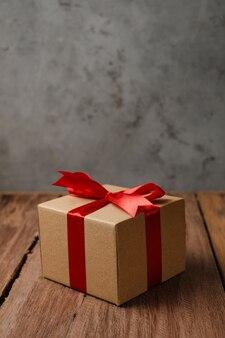Selektiver fokus der geschenkbox mit rotem band und liebespapier über rustikalem holztisch, draufsicht flach.