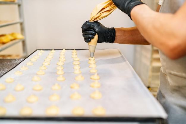 Selektiver fokus der hände eines konditoren mit süßwarenbeutel-quetschcreme in der konditorei-bäckerei