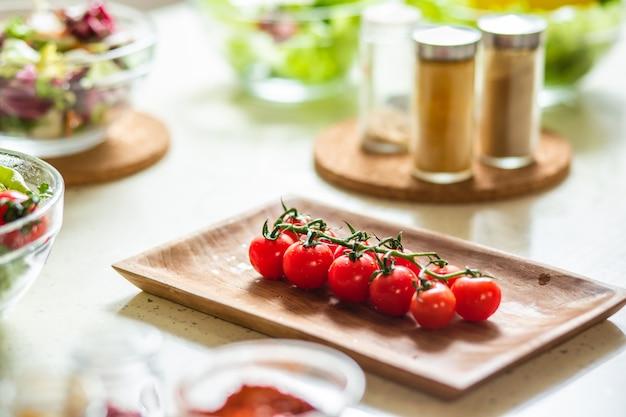 Selektiver fokus der holzplatte mit kirschtomaten. gewürze und schalen mit salaten