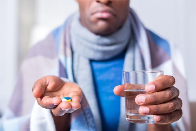 Selektiver fokus der medikamente in den händen eines netten unglücklichen kranken mannes