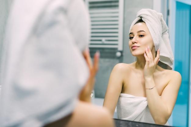 Selektiver fokus der schönen lächelnden jungen frau, die gesicht beim betrachten des spiegels berührt