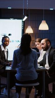 Selektiver fokus der workaholic-geschäftsfrau, die finanzdiagramme diskutiert