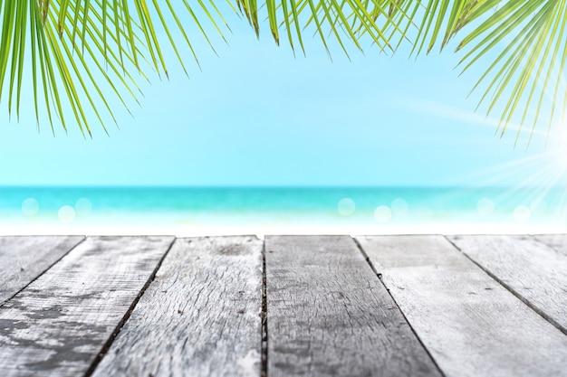 Selektiver fokus des alten holztisches mit schönem strand