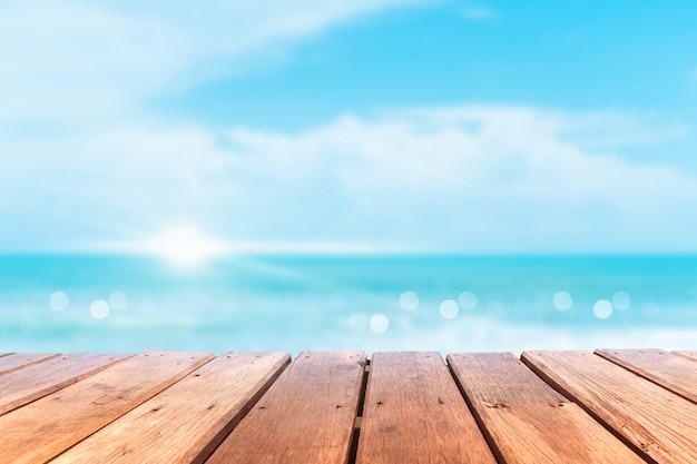 Selektiver fokus des alten holztisches mit schönem strandhintergrund für die anzeige ihres produktes.