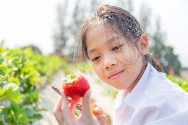 Selektiver fokus des glücklichen mädchenkindes, das frische rote organische erdbeeren im garten hält und schaut