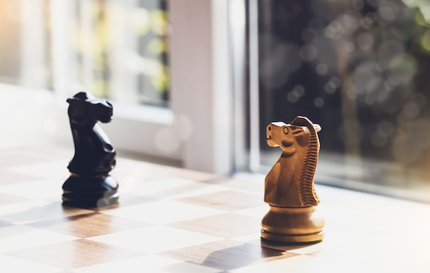 Selektiver fokus des holzritterschachs auf brettspiel mit verschwommenem hintergrund