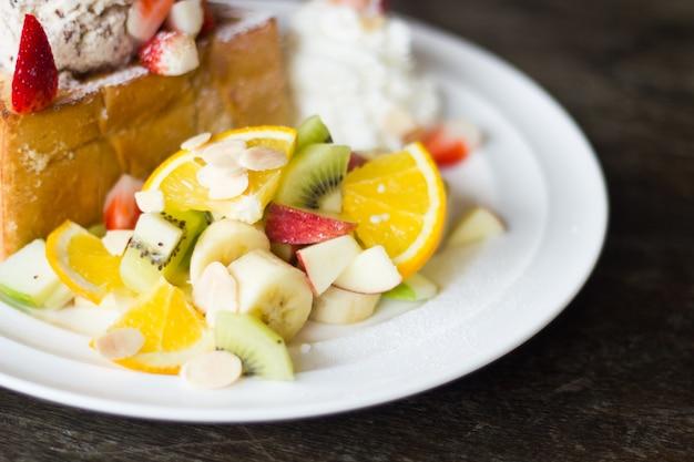 Selektiver fokus des honigtoasts mit frucht und eiscreme auf schlechter beleuchtung.