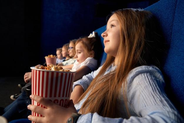 Selektiver fokus des hübschen kleinen mädchens, das popcorn-eimer hält und mit freunden in bequemen stühlen im kino sitzt. kinder, die zeichentrickfilm oder film schauen, spaß haben