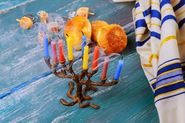 Selektiver fokus des jüdischen feiertags chanukkas mit traditionellem menorah, schaumgummiringe