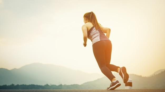 Selektiver fokus des läufers der jungen frau auf der straße bei dem sonnenuntergang.