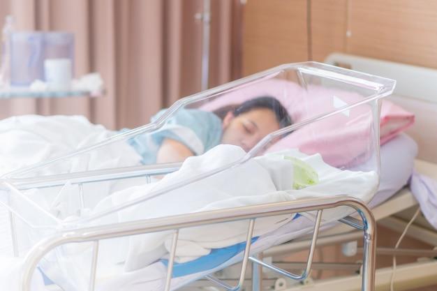 Selektiver fokus des neugeborenen babys und der neuen mutter, die in einem krankenhaus schlafen