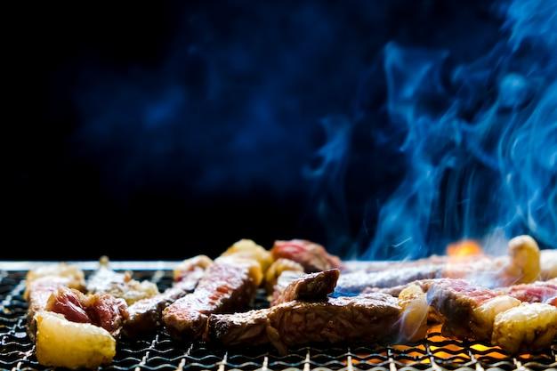 Selektiver fokus des saftig geschnittenen fleischrindfleischsteakgrills, der auf holzkohleofen mit rauch und feuerflamme auf schwarzem hintergrund grillt.