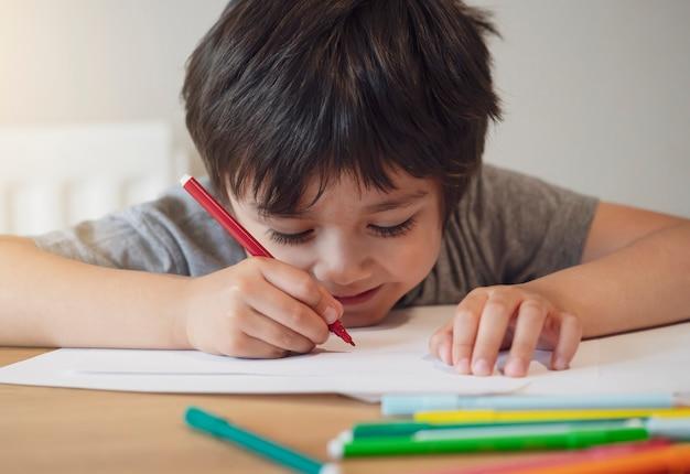 Selektiver fokus des schulkindjungen, der auf dem tisch sitzt, der hausaufgaben macht, glückliches kind, das roten stift hält, der auf weißem papier schreibt oder zeichnet, grundschule und heimschule, bildungskonzept