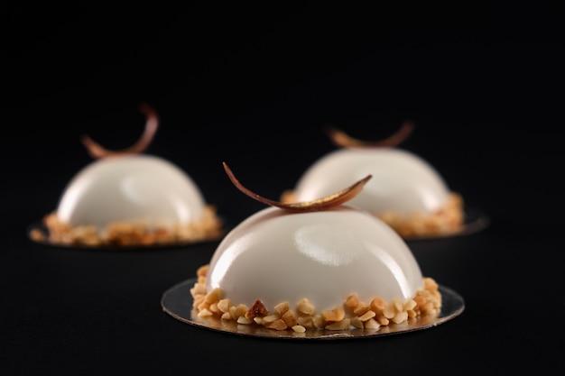 Selektiver fokus des weißen halbkugelkuchens, verziert mit nüssen und schokoladenfeder. desserts mit glatten oberflächen und spiegelglasur lokalisiert auf schwarzem hintergrund. leckeres süßes gericht in der cafeteria.