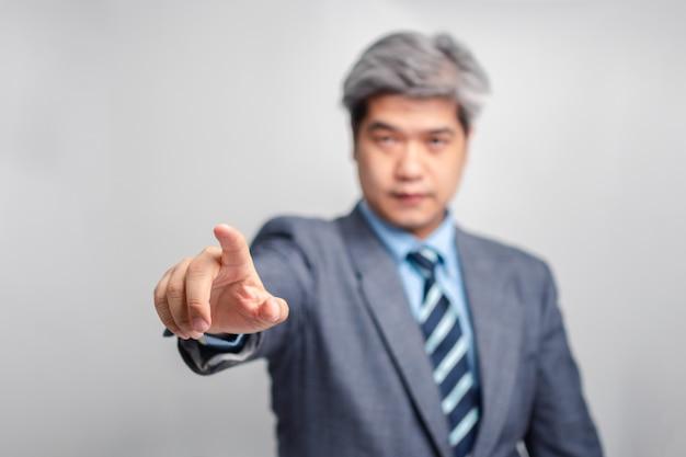 Selektiver fokus des zeigefingers des asiatischen leitenden geschäftsmannes in einem anzug auf weißem hintergrund (isolierter hintergrund). das konzept von kommunikation, technologie und verbindung