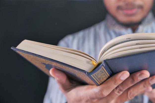 Selektiver fokus die hand des muslimischen mannes liest nachts den koran