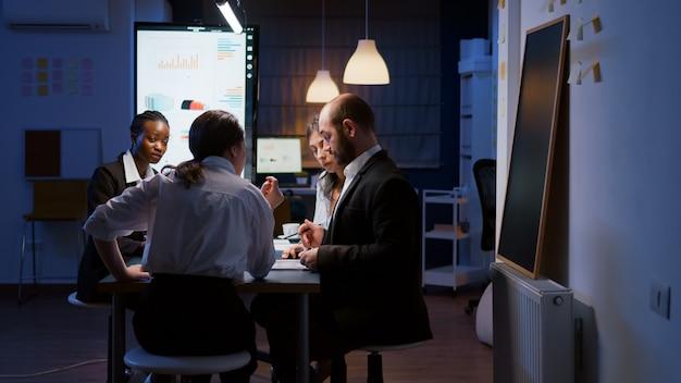 Selektiver fokus diverser multiethnischer geschäftsleute, die bis spät in die nacht überarbeiten