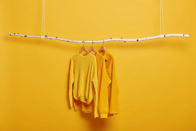 Selektiver fokus. drei kleidungsstücke auf kleiderbügeln. langärmelige gelbe pullover auf holzgestell nahe heller lebendiger wand.