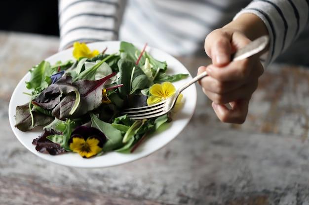 Selektiver fokus. eine schöne mischung aus salaten mit blumen auf einem weißen teller wird von einem mädchen gehalten. diätkonzept. gesundes veganes essen.