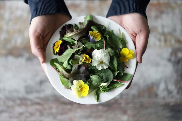 Selektiver fokus. eine schöne mischung aus salaten mit blumen auf einem weißen teller wird von einem mann gehalten. diätkonzept. gesundes veganes essen.