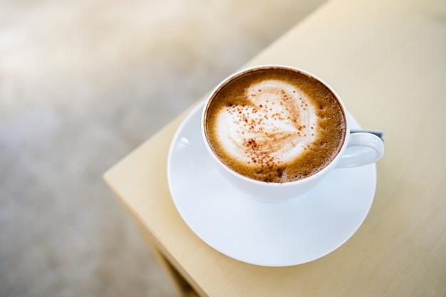 Selektiver fokus, eine tasse heißen latte-kaffee mit schöner milchschaum-latte-kunststruktur auf holztisch.