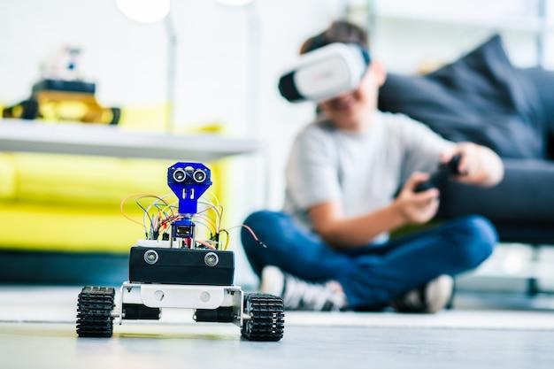 Selektiver fokus eines beweglichen robotergeräts, das von einem kleinen intelligenten jungen gesteuert wird, der eine vr-brille trägt