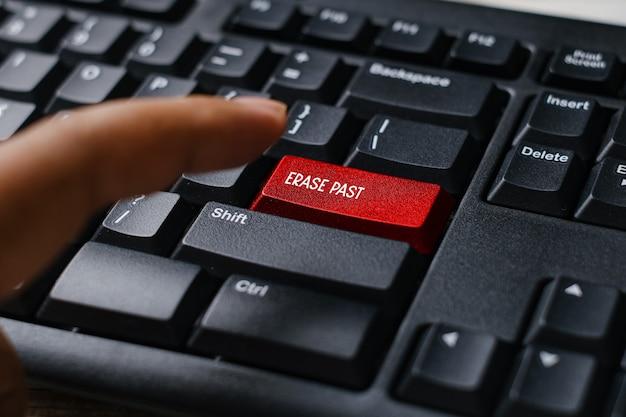 Selektiver fokus eines fingers und einer roten computertastatur, die mit erase past geschrieben wurde