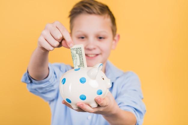 Selektiver fokus eines jungen, der banknote in das keramische sparschwein des tupfens gegen gelben hintergrund einfügt