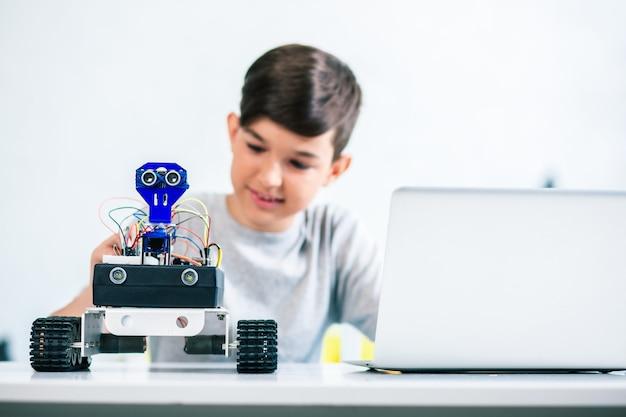 Selektiver fokus eines modernen roboters, der auf dem tisch steht, während ein kleiner begeisterter junge ihn testet