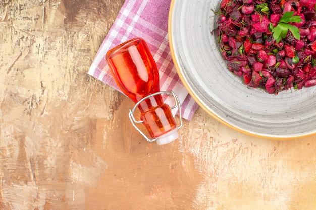 Selektiver fokus gesunder gemüsesalat mit olivenöl-dressing in einer roten flasche auf einem hintergrund mit kopierraum