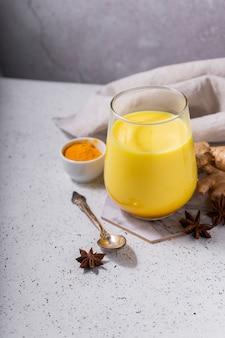 Selektiver fokus. gesundes ayurvedisches getränk goldene mandelmilch oder kürbis-kurkuma-latte mit kurkumapulver auf weißem hintergrund. kopierraum. trendiges asiatisches natürliches entgiftungsgetränk mit gewürzen für veganer
