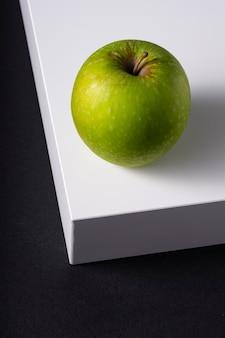 Selektiver fokus, grüner frischer apfel auf einem weißen würfel, auf einem schwarzen hintergrund