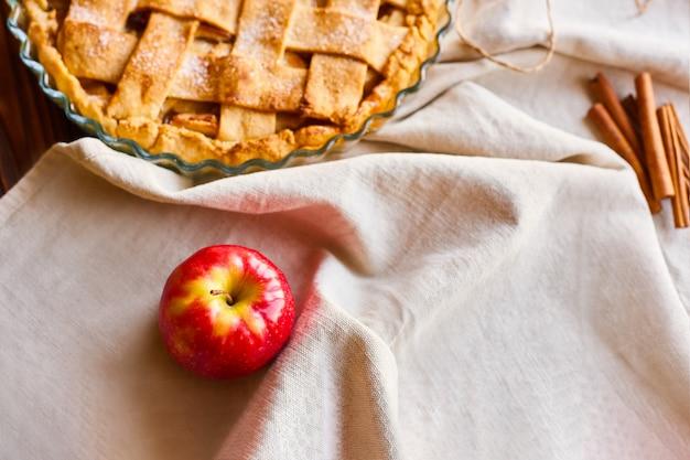 Selektiver fokus in der leckeren hausgemachten apfelkuchen-komposition. rohe äpfel auf leinenhandtuch. layout oder stillleben mit hausgemachter charlotte in form zum kochen