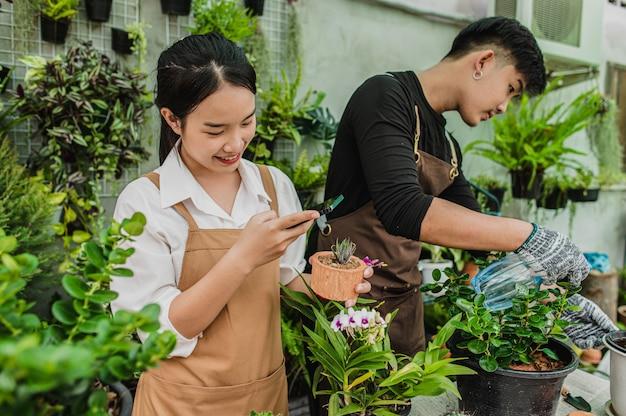 Selektiver fokus, junge frau benutzt smartphone, um ein foto vom kaktus zu machen, sie lächelt glücklich