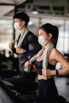 Selektiver fokus, junge sexy frau in maske mit sportbekleidung und smartwatch und verschwommener junger mann, sie laufen auf dem laufband, um im modernen fitnessstudio zu trainieren