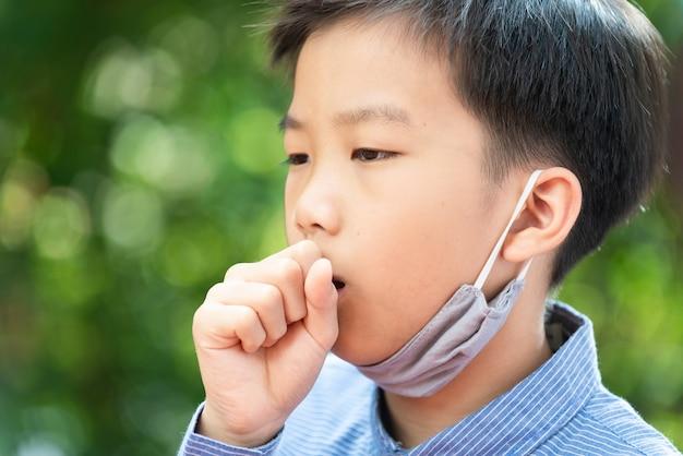 Selektiver fokus junger asiatischer junge mit gesichtsmaske, visus zu schützen, auf großem hintergrund