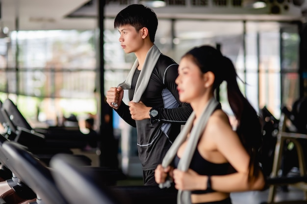 Selektiver fokus junger mann, verschwommene junge sexy frau im vordergrund mit sportbekleidung und smartwatch, sie laufen auf dem laufband, um im modernen fitnessstudio zu trainieren,