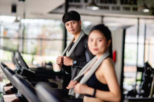Selektiver fokus, junger sportmann und unscharfes porträt sexy frau in sportbekleidung auf laufband, sie trainieren im modernen fitnessstudio, lächeln, kopierraum
