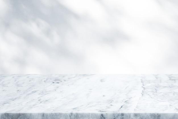 Selektiver fokus. murmeltischplatte auf unscharfem schatten des baumes auf weißem wandhintergrund.