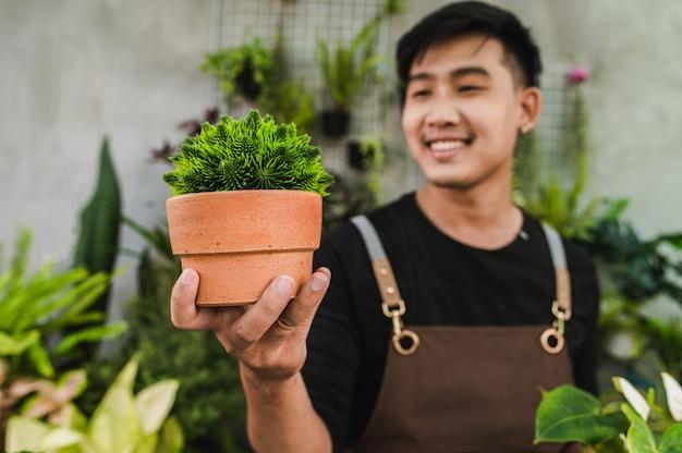 Selektiver fokus, nahaufnahme junger gärtner, der eine schöne zimmerpflanze mit stolz hält