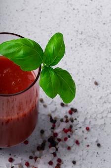 Selektiver fokus, natürliches tomatengetränk, tomatensaft mit gewürzen und einem zweig grünem basilikum