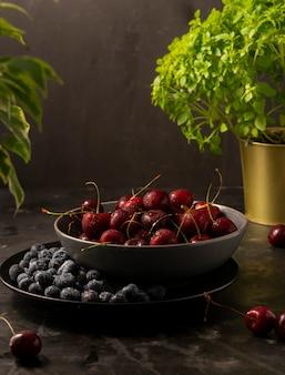 Selektiver fokus, reife kirschen und blaue blaubeeren mit wassertropfen in einer dunklen küchenschale, auf einem dunklen hintergrund, vertikale position, rustikaler stil