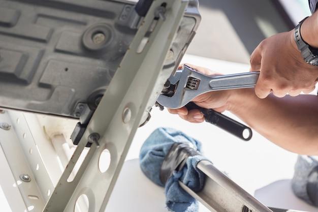 Selektiver fokus reparatur von klimaanlagen, technikermann hände mit einem schraubenschlüssel zur befestigung moderner klimaanlagen