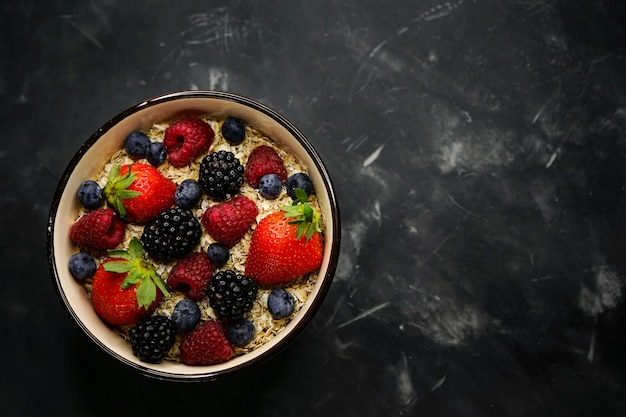 Selektiver fokus, richtige ernährung, gesundes frühstück, tiefe platte mit müsli, haferflocken, frischen erdbeeren, himbeeren, blaubeeren und brombeeren