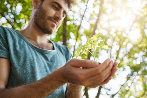 Selektiver fokus. schließen sie herauf porträt des jungen dunkelhäutigen mannes mit bart im blauen hemd, das kleine pflanze in den händen hält. mann, der im garten am sonnigen tag arbeitet, der sich entspannt und glücklich fühlt.