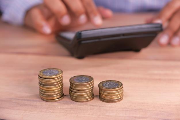 Selektiver fokus. stapel münzen auf tisch und mann mit taschenrechner auf platz