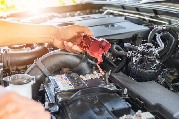 Selektiver fokus, technikermannhand, die autobatterie auf automotorsystem überprüft