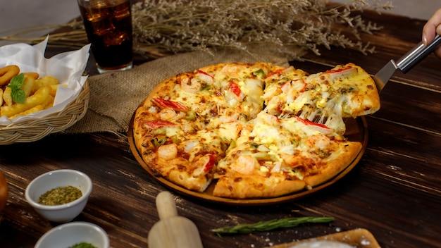 Selektiver fokus und nahaufnahme auf einem stück hausgemachter meeresfrüchtepizza mit doppeltem käse auf spachtel oder schaufel mit unscharfem hintergrund von holztisch, sackleinen, zutaten und bratkartoffeln. lebensmittelkonzept.